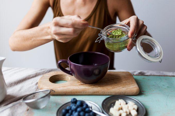 Woman preparing matcha latte at home