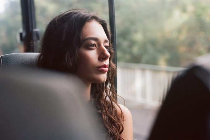 A young woman rides a bus and stares serenely out the window