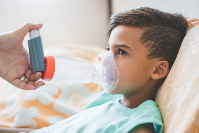 Woman with son doing inhalation with nebulizer at home