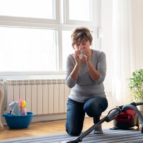 Senior woman cleaning carpet with a vacuum cleaner at home