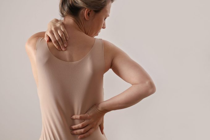 Woman with back and neck pain. Pure posture concept