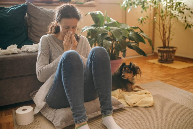 Woman suffering from allergies and flu at her home