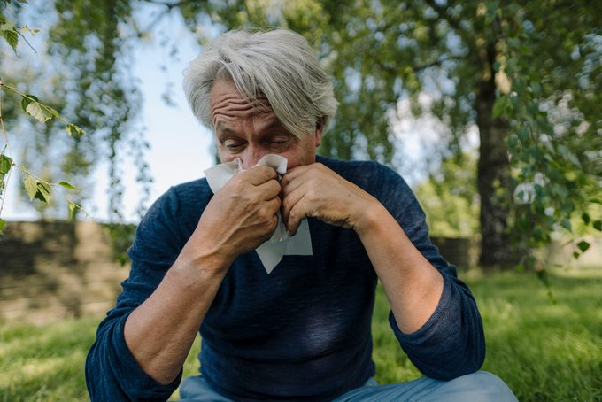 man blowing nose while sitting in field