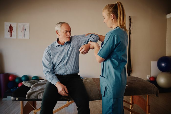 Young female physiotherapist helping senior man with elbow exercise in clinic - young female doctor helping senior patient