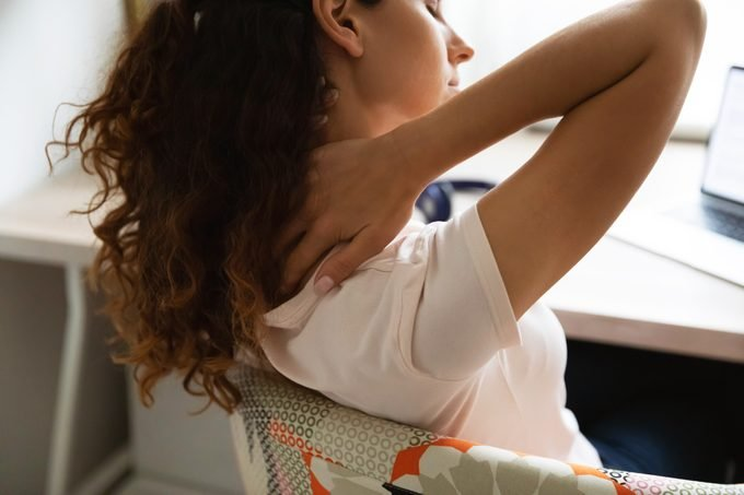 woman sitting at desk with neck pain