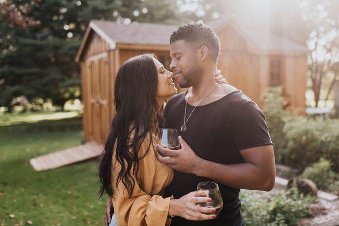 Couple holding wineglass while doing romance standing at backyard