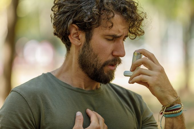 A Man is Using an Asthma Inhaler in Public Park.