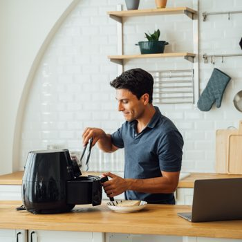 Man using air fryer and laptop in kitchen