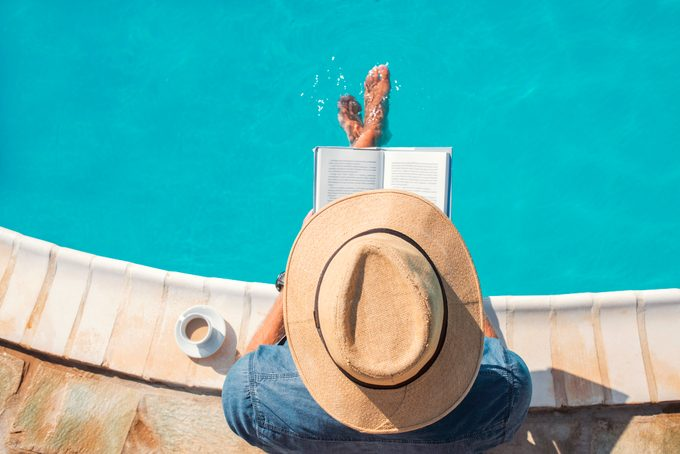 overhead shot of man wearing a hat and reading a book by the pool during summertime