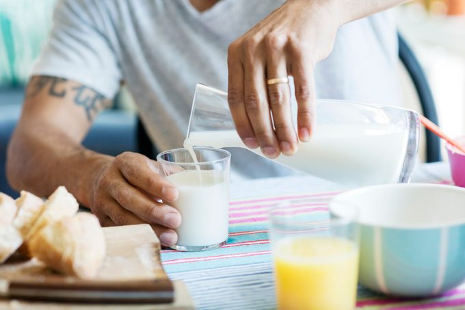 Midsection of man pouring milk in drinking glass at table