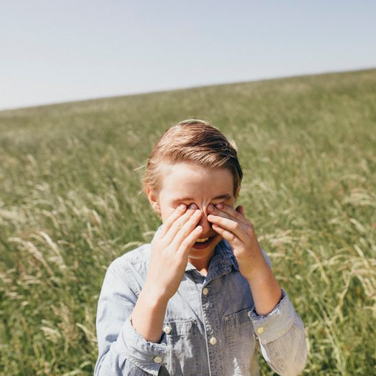 young Boy in a field rubbing his eyes
