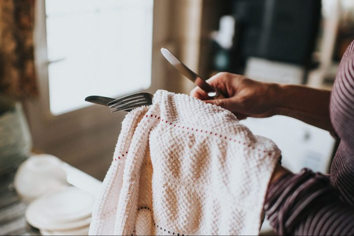 Woman drying Dishes with dish towel close up