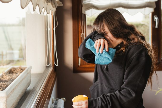 young woman cleaning a house and suffering from spring allergy headache