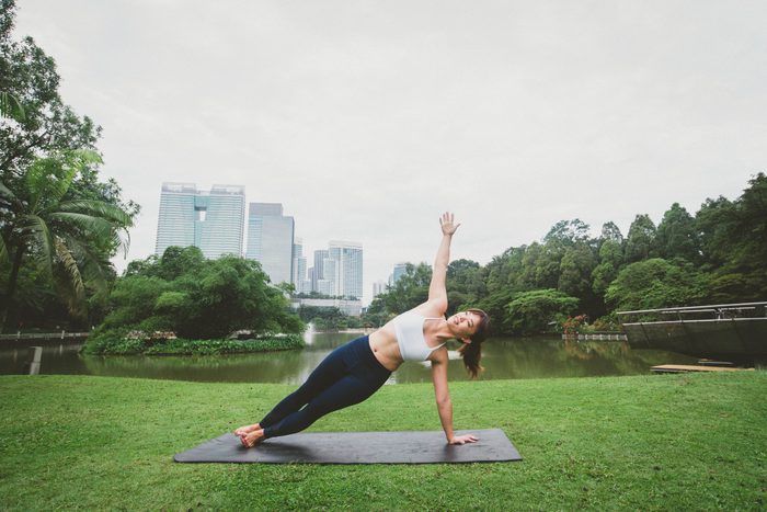 Young fitness woman practicing yoga side plank pose together relax in nature