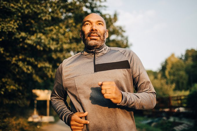 Man jogging in park during sunset
