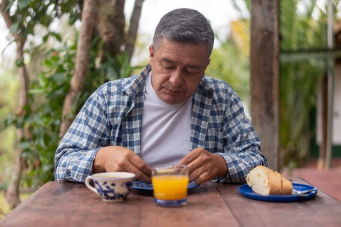 Adult man eating breakfast outdoors at his rural house