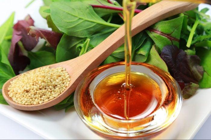 pouring sesame oil on salad