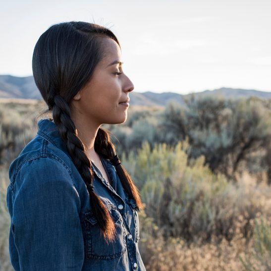Young Native American woman outdoors at sunset