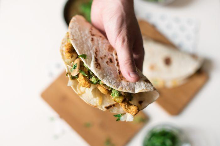 Human hand holding homemade chicken taco