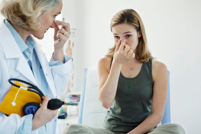 woman with sinus infection talking to ENT doctor