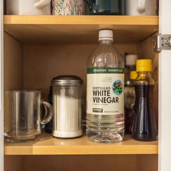 White Vinegar bottle on shelf in kitchen cabinet