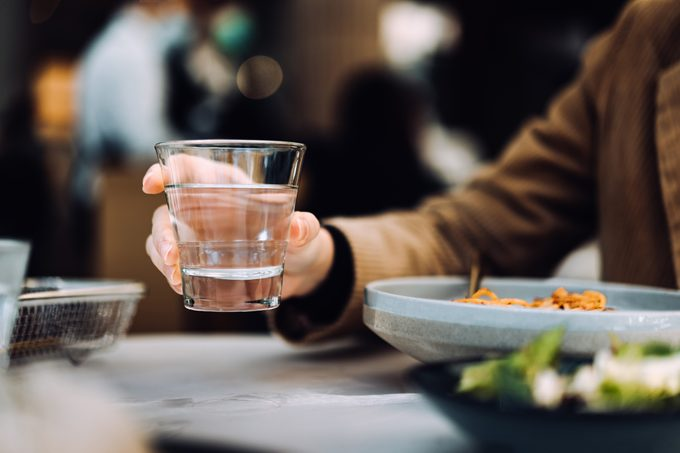 Close up of young woman drinking a glass of water while having meal in a restaurant.