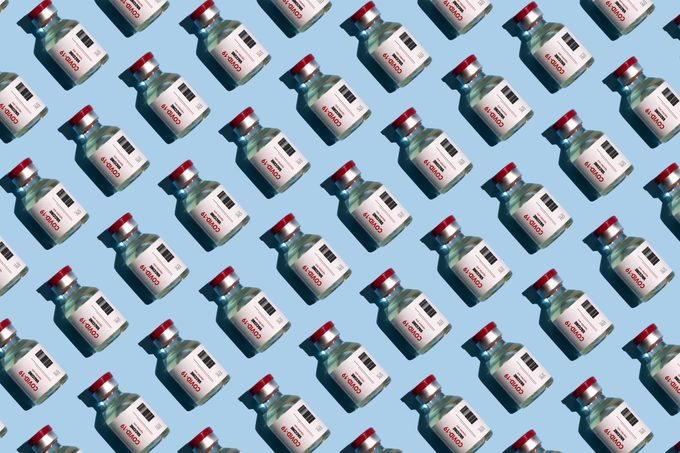 Repeated covid vaccine vials on blue background