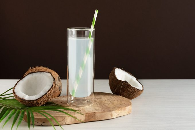 glass of coconut water on brown studio background