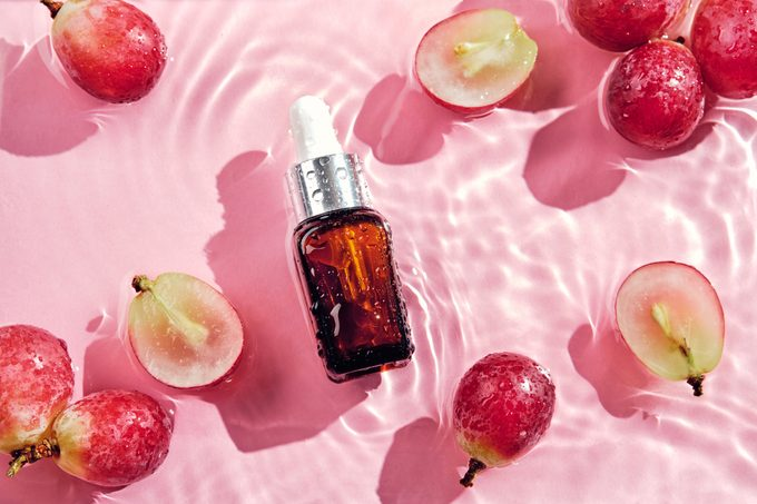 grapeseed oil in cosmetic bottle on pink water background