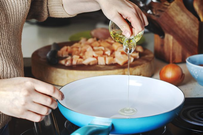 Woman pouring olive oil into skillet in kitchen while cooking