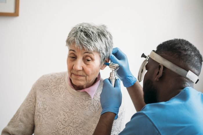 An older woman having her ears checked by the ear doctor