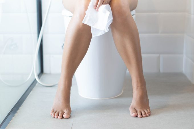 lower half of woman sitting on toilet with tissue paper in hand