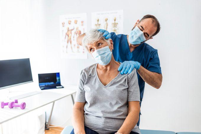 doctor examining patient's neck pain