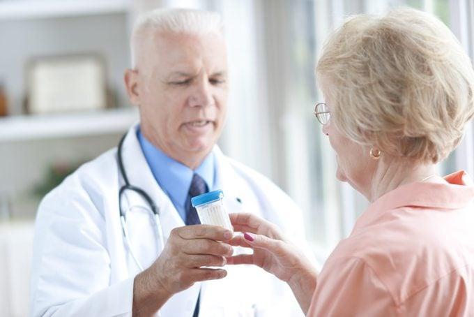 doctor handing patient a urine sample cup