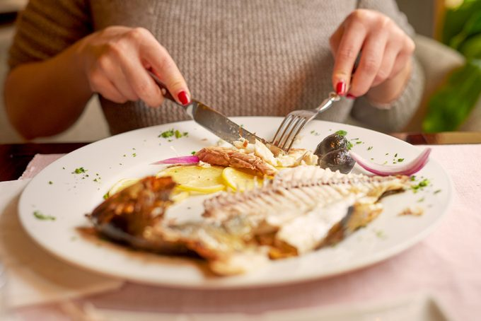 woman eating fish for dinner