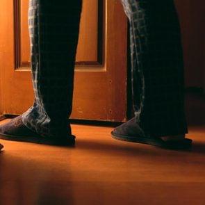 Adult man walking into bathroom at night
