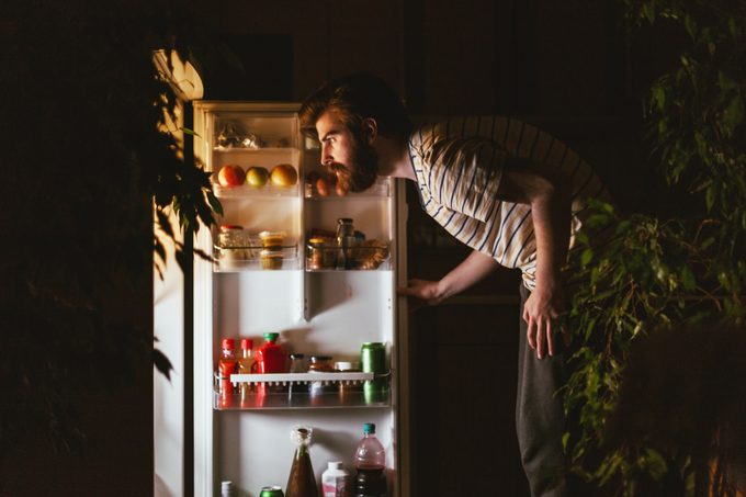man looking in refrigerator late at night