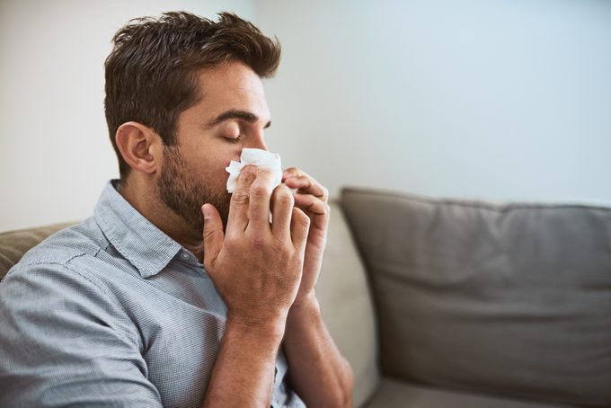 close up of young man blowing his nose while sitting on couch at home