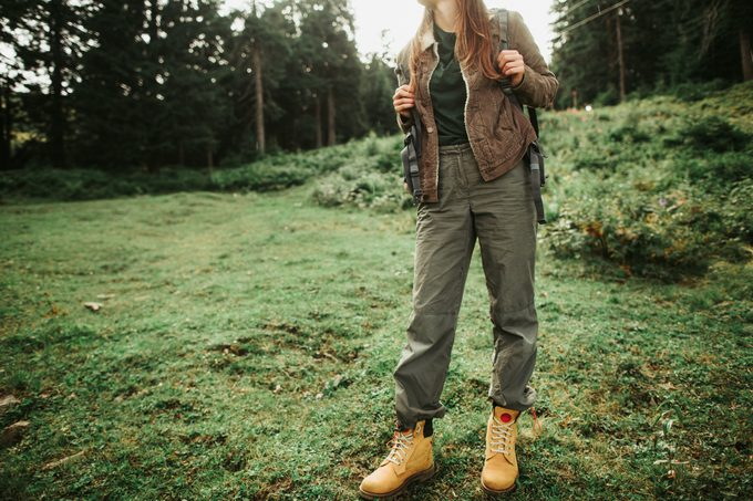 young woman wearing hiking pants standing on grass