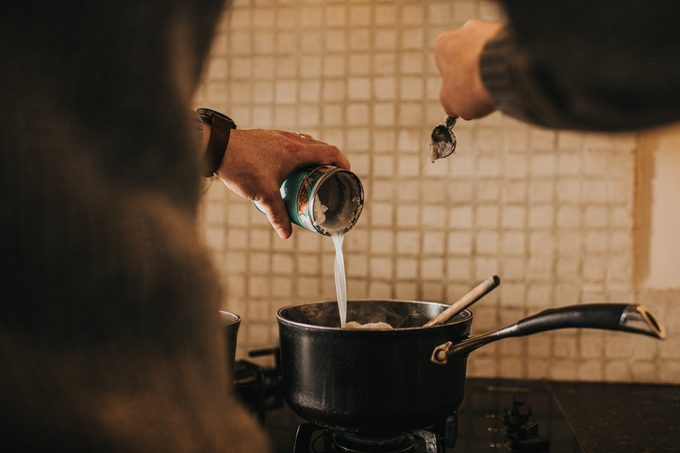 pouring coconut milk into saucepan over the stove