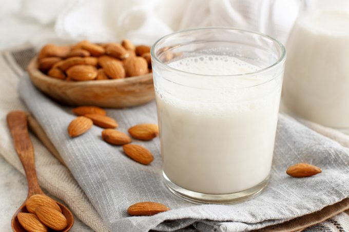 glass of almond milk surrounded but almonds
