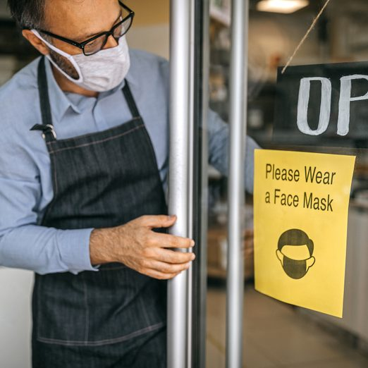 Man at doorway with a sign requesting to wear protective face mask on reopening of shop during coronavirus outbreak