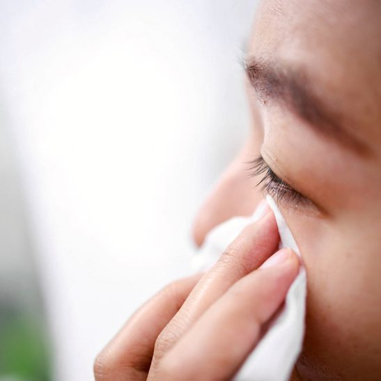 young woman wiping eye with tissue