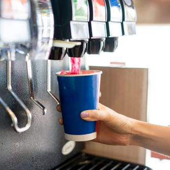 close up of person getting a soda from a fountain drink machine