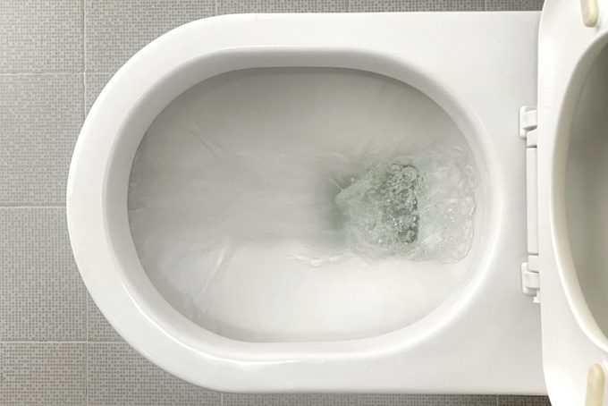 Water flushing down toilet bowl