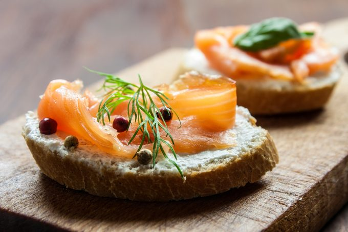 Smoked salmon canapes on a brown wooden plate