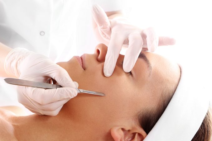 dermatologist dermaplaning woman's face with scalpel object
