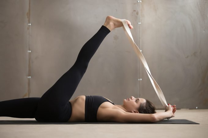 young woman using a stretch strap for yoga