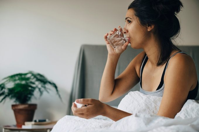 woman drinking water while sitting in bed at home