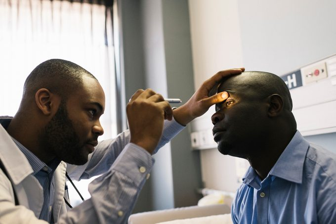 Young doctor uses ophthalmoscope to examine patient's eye